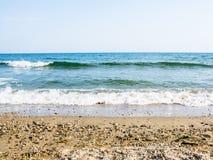 Denne pływowe fala z bielem pienią się na pogodnej piaskowatej plaży w kurorcie Fotografia Royalty Free