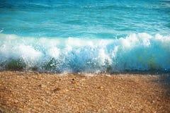 Denny brzeg przy lato słonecznym dniem, błękitne fala nawadnia teksturę w morza śródziemnomorskiego tle Obrazy Stock