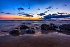 Denny zmierzchu seascape z mokrymi skałami Obraz Stock
