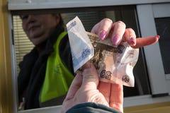 A denominação de 50 rublos em sua mão esticou para fora para pagar f Fotos de Stock