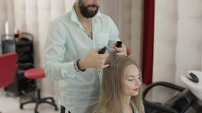 A denominação profissional do cabeleireiro adiciona o pó do cabelo no cabelo modelo video estoque