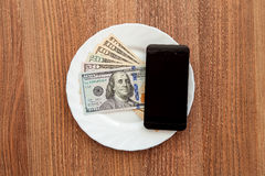 Denomination dollars and a black business phone. Stock Image