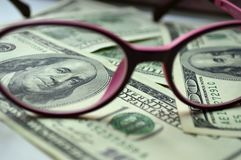 Denominations in the amount of $ 100 view through the glasses. Denominations in the amount of $ 100 view through rose-colored glasses Royalty Free Stock Image
