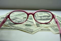 Denominations in the amount of $ 100 view through the glasses stock photography
