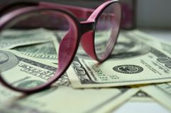 Denominations in the amount of $ 100 view through the glasses. Denominations in the amount of $ 100 view through rose-colored glasses Royalty Free Stock Images