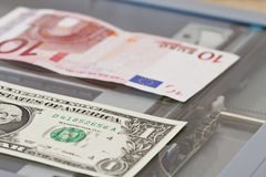 Denominations of one dollar and ten euros lie on scaner Royalty Free Stock Photos