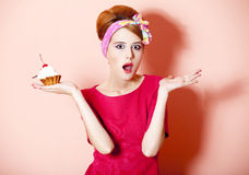 Denomine a menina do redhead com o bolo no fundo cor-de-rosa. Fotografia de Stock Royalty Free