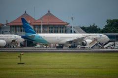 DENPASAR/BALI- 11-ОЕ АПРЕЛЯ 2019: Стоянка авиакомпании Garuda Индонезии на рисберме международного аэропорта Ngurah Rai Бали окол стоковые фотографии rf