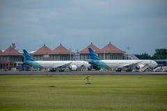 DENPASAR/BALI- 11-ОЕ АПРЕЛЯ 2019: Стоянка авиакомпании Garuda Индонезии на рисберме международного аэропорта Ngurah Rai Бали окол стоковые изображения rf