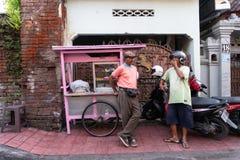 DENPASAR/BALI-, 20. APRIL 2019: ein Straßenfleischklöschenverkäufer benutzt einen rosa Wagen und trägt ein rosa Hemd plaudernd mi lizenzfreie stockfotos