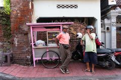 DENPASAR/BALI-APRIL 20 2019: a street meatball seller uses a pink cart and wears a pink shirt chatting with his buyers on the royalty free stock photos