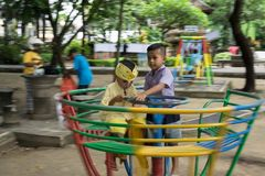DENPASAR/BALI-DECEMBER 28 2017年:使用在草坪的两个男孩 他们中的一个打与小配件的比赛,象使上瘾 库存照片