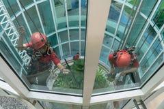 DENPASAR/BALI-JUNE 29 2018: Dwa janitors czyścili okno lokalizować przy wzrostem budynek używać zupełnego bezpieczeństwo fotografia royalty free