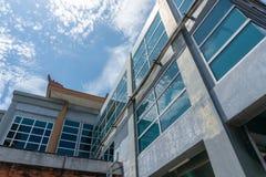 DENPASAR/BALI-, 27. MÄRZ 2019: Das Gebäude mit Glasfenstern benutzt eine kleine Balineseverzierung auf dem Dach während das sonni lizenzfreies stockfoto