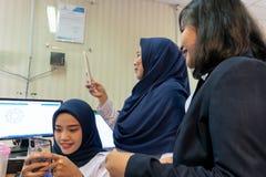 DENPASAR/BALI-MARCH 27 2019年:使用hijab的妇女在她的手机发短信,当她的看她和做时的其他朋友 免版税库存图片
