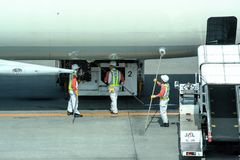 Workers preparing the plane to the flight. In the airport of Denpasar. royalty free stock image