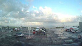 DENPASAR, INDONÉSIA - EM MARÇO DE 2016: Vista terminal da janela em planos no campo da decolagem cedo na manhã dentro video estoque