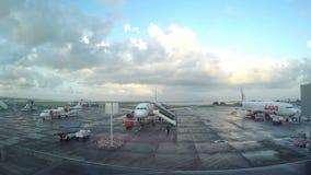 DENPASAR, INDONESIA - MARZO DE 2016: Visión terminal desde la ventana en los aviones en el campo del despegue temprano por la mañ almacen de video