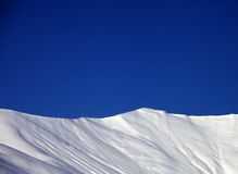 denpiste lutningen och blått gör klar himmel i trevlig vinterdag Royaltyfri Bild