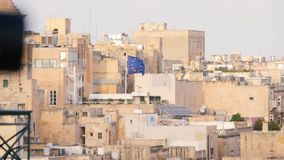 Dense buildings, historic stone houses in heat and dust, Middle Ages, desert, Africa, Malta, EU flag. Dense buildings, historic stone houses in heat and dust stock footage