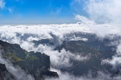 Dense clouds over mountains range on sunny day on Portuguese island of Madeira. Dense clouds over mountains range on sunny day. View from Pico do Arieiro on royalty free stock image