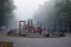 Dense fog in the city. Early morning in Kyiv. Empty playground is waiting little kids Royalty Free Stock Image