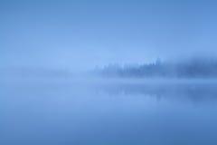 Dense fog over lake in Alps Stock Photo