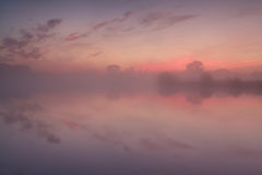 Dense fog over lake at dramatic sunrise Royalty Free Stock Images