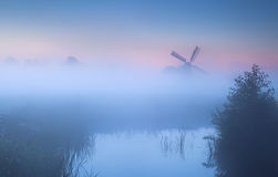 Dense fog over river and windmill Stock Photos
