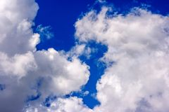 Dense white clouds on a beautiful summer blue sky royalty free stock photography