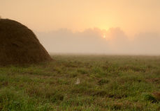 Dense morning fog over the meadow and haystack just after sunri royalty free stock photo