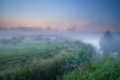 Dense morning fog and windmill Royalty Free Stock Image
