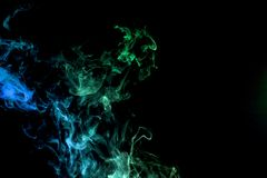 Background from the smoke of wipe. Dense multicolored smoke of blue, green on a black isolated background. Background of smoke vape Stock Photo