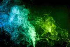 Background from the smoke of vape. Dense multicolored smoke of   green and blue colors on a black isolated background. Background of smoke vape Royalty Free Stock Photo