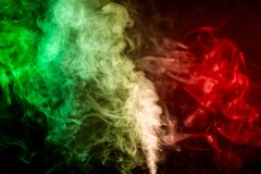 Background from the smoke of vape. Dense multicolored smoke of   green, red and blue colors on a black isolated background. Background of smoke vape Royalty Free Stock Photography