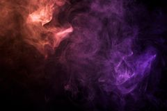 Background from the smoke of vape. Dense multicolored smoke of  pink and red colors on a black isolated background. Background of smoke vape Stock Photos