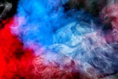 Dense multicolored smoke of red, purple and pink colors on a black isolated background. Background of smoke royalty free stock photography