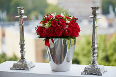 Dense red bouquet of roses and berries, brilliant in the iron bucket  two metal candle holders Stock Photos