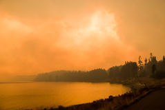 Yellowstone Firestorm. Dense smoke obscures the sky above Yellowstone Lake as a forest fire races toward the shoreline Stock Photo