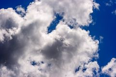 Dense white clouds on a beautiful summer blue sky Royalty Free Stock Photos