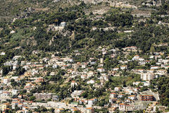 Densely populated city on mountain. Monte Carlo, Monaco - September 20, 2015: view of mountain with densely populated city with residential buildings green trees Stock Photography