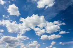 Densely puffy clouds on fresh cheerful blue sky Stock Photos