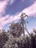 denspänning kraftledningen mot bakgrunden av gröna träd och en lavendelhimmel med vit fördunklar på en solig dag för sommar Royaltyfri Foto