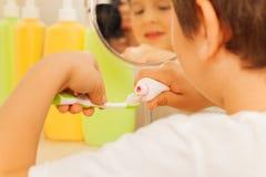 Dentífrico de espalhamento do rapaz pequeno em uma escova de dentes fotos de stock royalty free