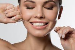 Dent émouvante de jeune femme joyeuse par le fil dentaire Photographie stock