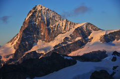 Dent Blanche at sunset. West face of Dent Blanche (4357m) in the Swiss Alps  at sunset.  On the right the Dent Blanche refuge can be seen on it's rocky spur Royalty Free Stock Photography