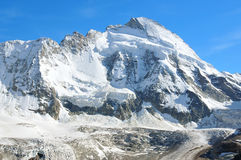 Dent d'Herens. The magnificent Dent (or tooth of) d'Herens in the swiss alps above Zermatt, connected to the Matterhorn. At its foot the Zmutt glacier Royalty Free Stock Photo