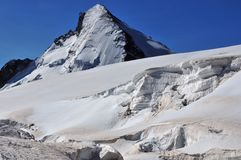 Dent d'Herens and Crevasses at the Pass. The north face of the Dent d'herens (4171m) in the Swiss Alps. In the foreground, deep crevasses at the Herens Pass, at Royalty Free Stock Photo