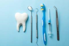 Dent et instruments dentaires sur le fond bleu Demande de r?glement dentaire Outils de dentiste miroir, crochet, brucelles, serin photographie stock libre de droits