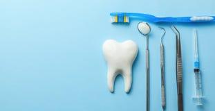 Dent et instruments dentaires sur le fond bleu Demande de r?glement dentaire Outils de dentiste miroir, crochet, brucelles, serin image stock
